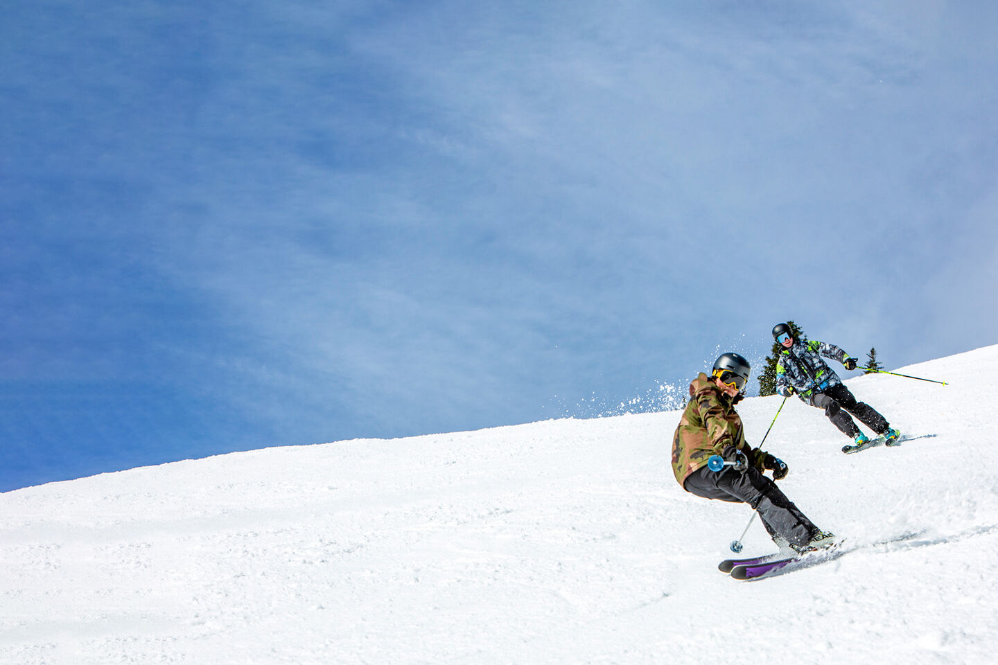 skier and snowboarding riding on mountain blue bird day