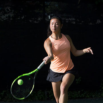 woman playing tennis with racquet and ball