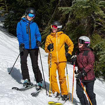 Women on skis laughing with ski poles by trees