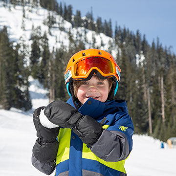 Kid boy smiling in ski jacket with snowball