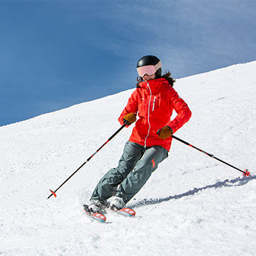 Woman skiing carving turns with ski poles helmet and goggles