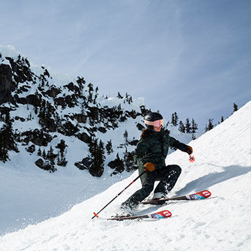 woman skiing carving turns with ski poles