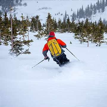 Man skiing backcountry with backpack through fresh powder