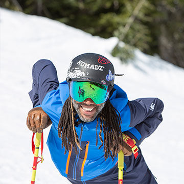 Man on skis with ski poles helmet and goggles