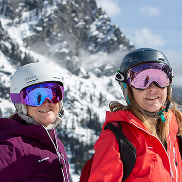 Women on skis with helmet and goggles blue bird day