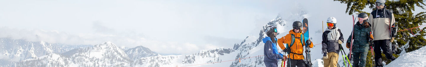 men standing on mountain holding skis and snowboards with helmets