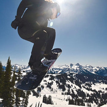 View from behind snowboarder jumping