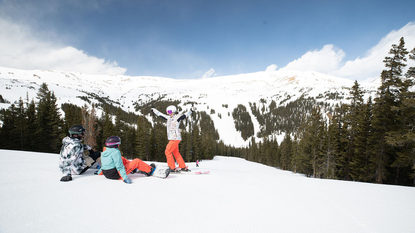 family in rental skis sitting at top of mountain
