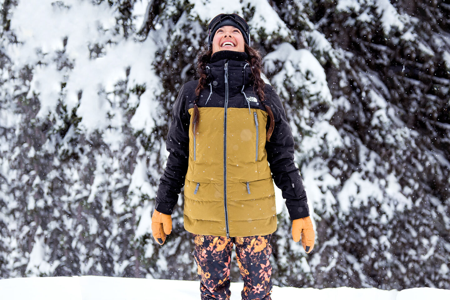 woman in the north face clothing smiling by trees