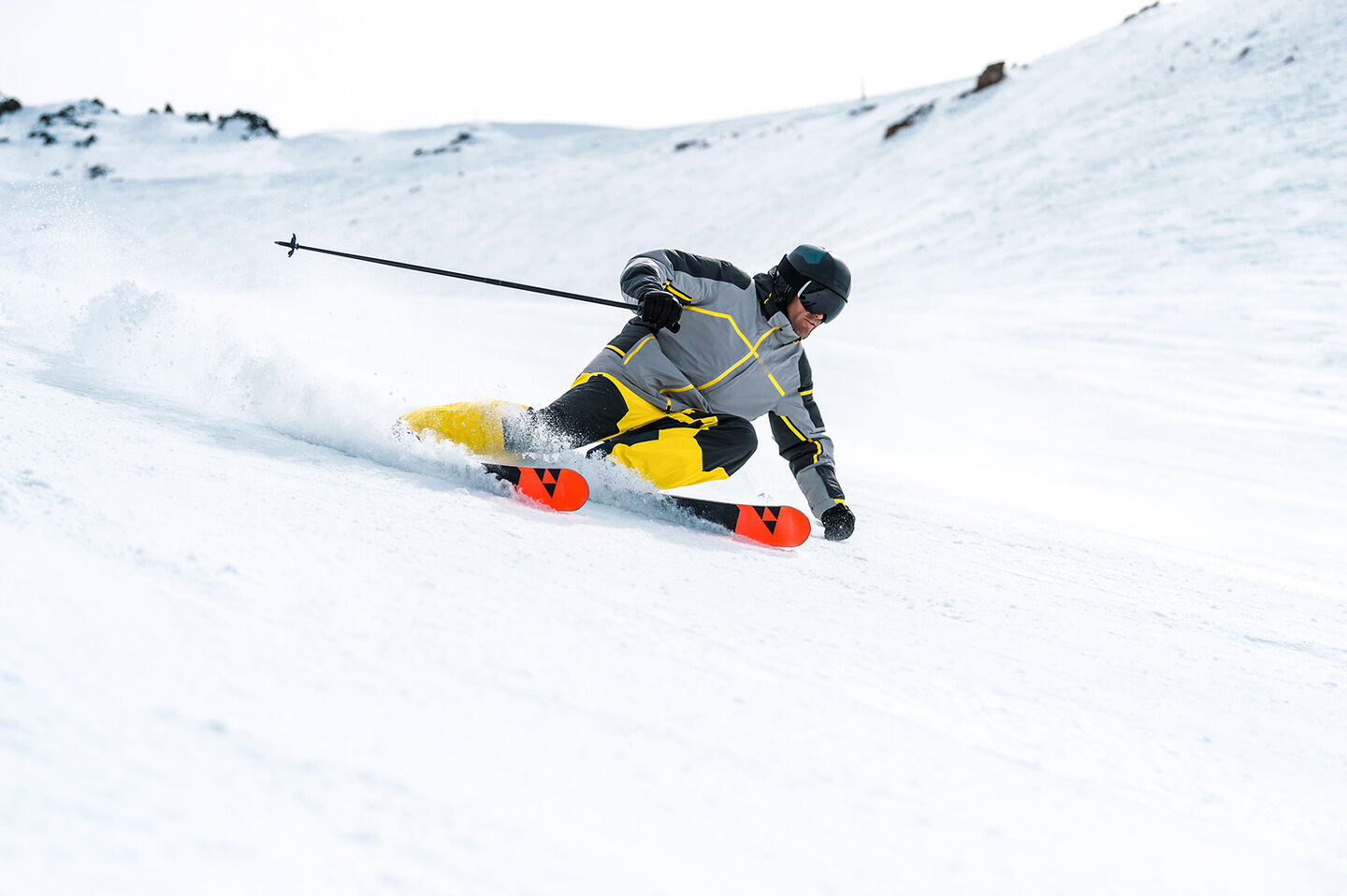 Male skier in Spyder apparel carving through snow