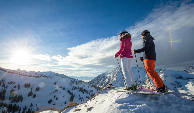 Male and female skiers enjoying view from summit of mountain
