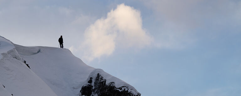 Skier at the summit of a snowy mountain peak