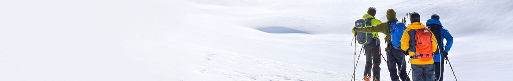 men hiking backcountry with ski skins and poles
