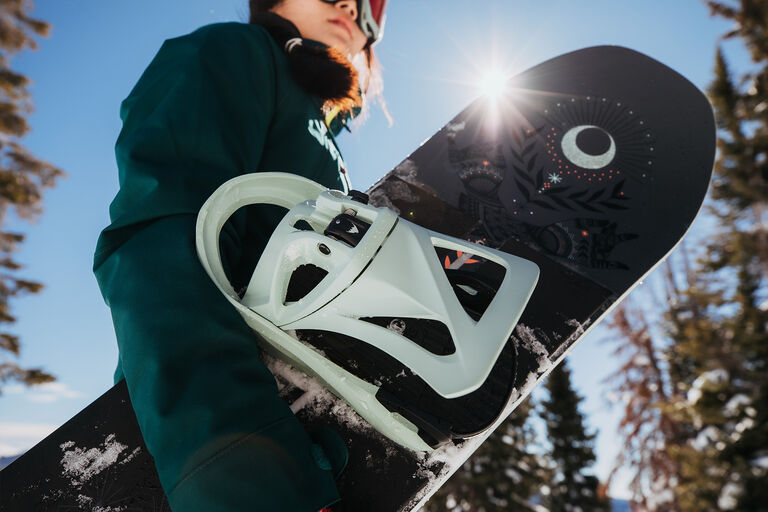 woman holding snowboard with binding