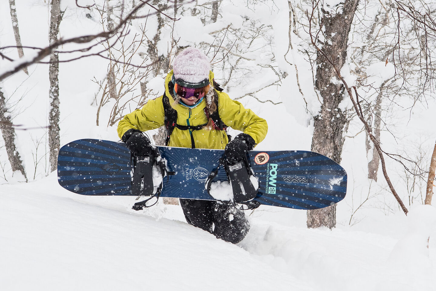woman carrying snowboard in powder