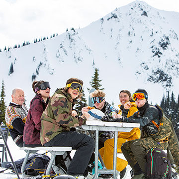 Men and Women skiers and snowboarders laughing at picnic table on mountain
