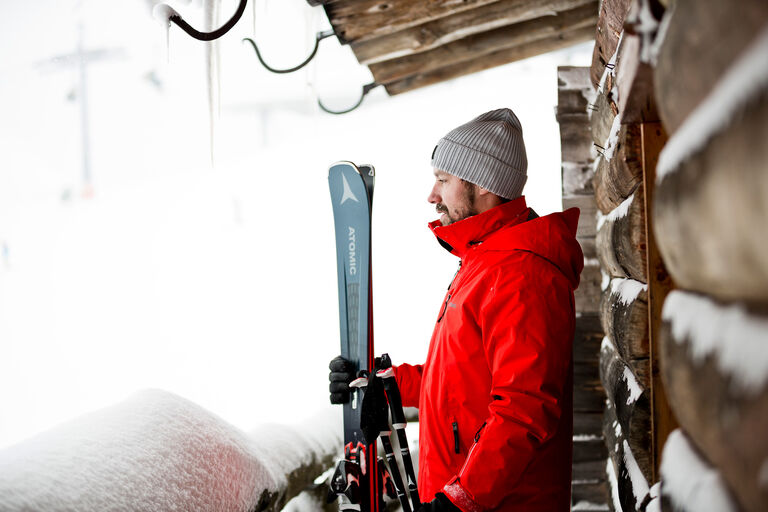 Man staring out into freshly fallen snow, anticipating an amazing ski day