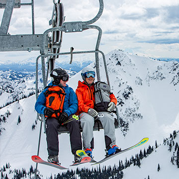 man and woman on ski lift laughing with backpacks and skis