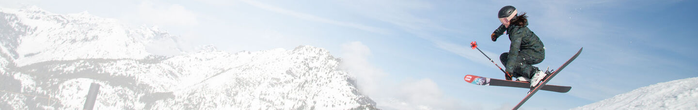 woman skier going off jump getting air on mountain